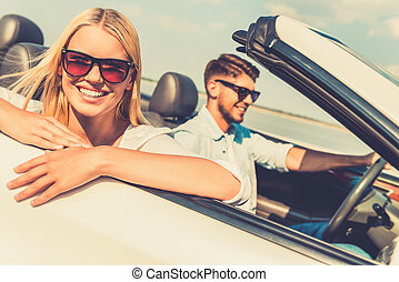 Feeling relaxed and free. Happy young woman leaning at the vehicle door and looking at camera while her boyfriend sitting near and driving convertible