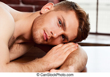 Feeling relaxed. Handsome young shirtless man looking at camera while leaning at the table