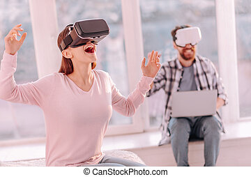 b5b05e6b6c6 Virtual game. Vigorous optimistic gorgeous woman shouting while sitting on  bed and playing in VR game · Young woman in VR glasses shouting something