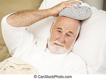 Feeling Sick - Senior man home sick with a cold, flu, or...