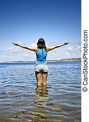 Feeling the breeze - Beautiful woman in the water feeling ...