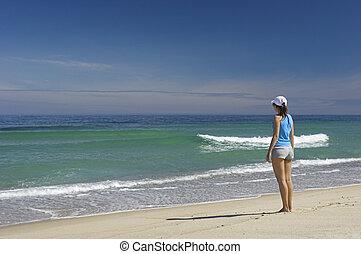 Feeling the breeze - Beautiful woman walking on the beach...