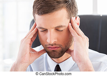 Feeling tired and depressed. Depressed young man in shirt and tie holding head in hands and keeping eyes closed while sitting at his working place