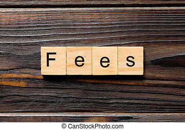 Fees word written on wood block. Fees text on wooden table ...
