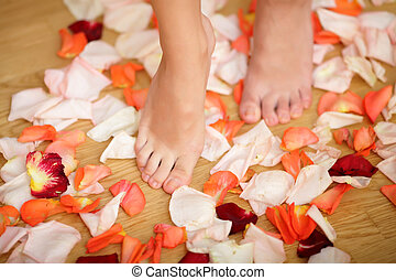 Feet and rose petals on the ground