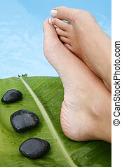 Feet by Pool - Woman\\\'s feet by blue pool with pebbles and...