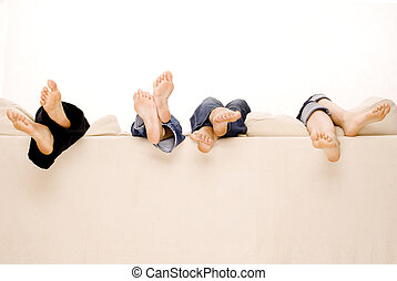Four pairs of feet hang over the back of a beige sofa