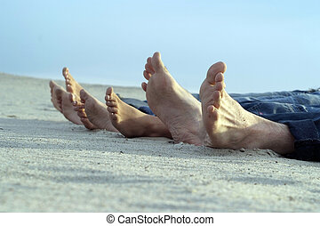 feet four people lying on light sand