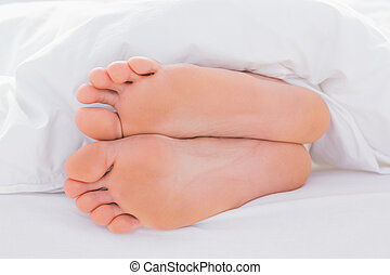 Feet in a bed