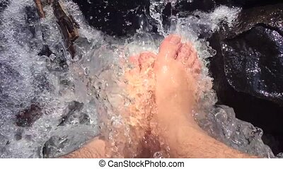 Feet in a natural stream during hiking trip