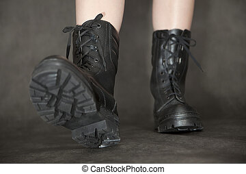 Feet in black leather army boots
