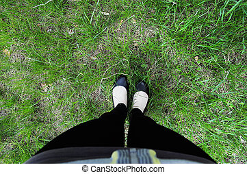 Feet in boots on grass background