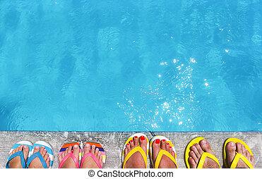 Feet in flip flops on stone background