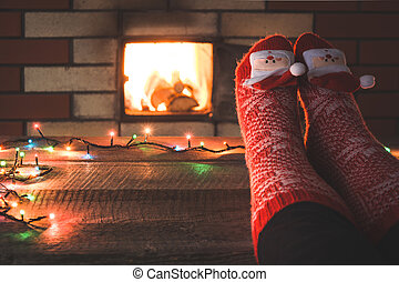 Feet in red socks by the fireplace. Relaxes by warm fire and warming up her feet in christmas socks. Christmas holiday.