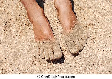 boy's feet in yellow fine sand on beach closeup