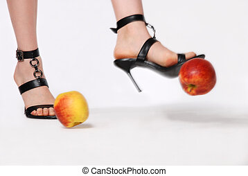 Feet in sandals kick apple