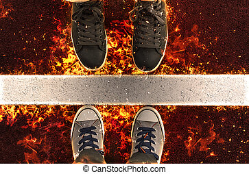 Feet in sneakers, standing next to yellow street lines in flame.