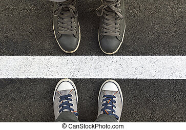 Feet in sneakers, tanding next to yellow street lines.