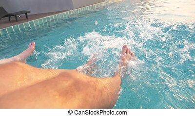 feet in the pool sprinkle water, spray in slow motion,