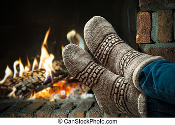 Feet in wool socks warming at the fireplace - Relaxing at...