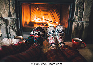 Feet in woollen socks by the Christmas fireplace. Family...
