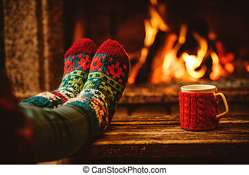 Feet in woollen socks by the Christmas fireplace. Woman...
