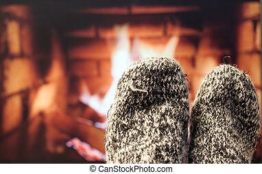 Feet in woollen socks by the fireplace