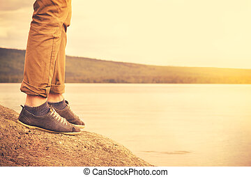 Feet man walking outdoor Travel Lifestyle vacations concept with lake and sun on background retro colors