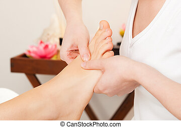 Feet receiving a massage in a spa setting (close up on feet)