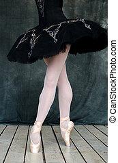 feet of a ballerina in  black dress on wooden floor