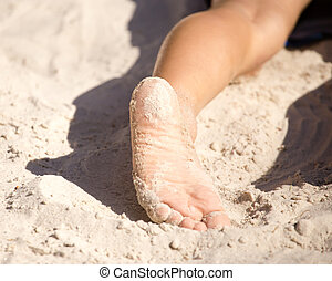Feet of a boy playing in the sand