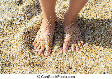 Feet of a child in the sand
