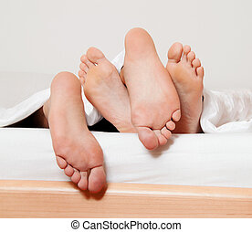 feet of a couple in bed. - dents a couple feet in bed. love,...