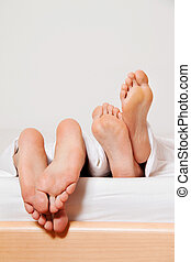 feet of a couple in bed.