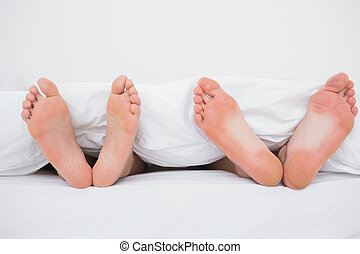 Feet of a couple in bed