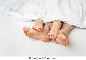 Feet of a couple in bed under the blanket