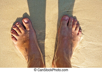 feet of a man in the fine sand