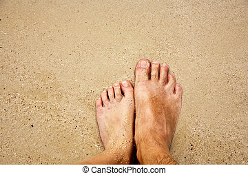 feet of a man in the fine sand surrounded by saltwater