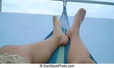 feet of a man lying down in a hammock