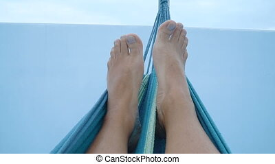 feet of a man lying down in a hammock