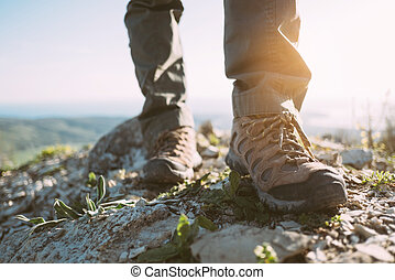 Feet of a traveler in trekking boots.