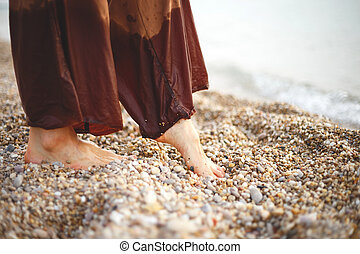 feet of a woman in brown trousers in pebbles on the seashore