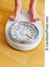 Feet of a woman on bathroom scale - Turn the feet of a woman...
