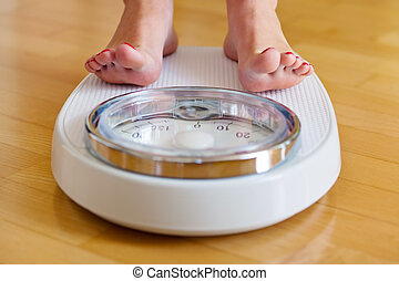 feet of a woman on bathroom scales - the feet of a woman ...