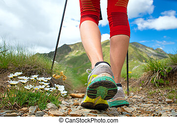 Feet of a woman who hikes in the mountains with nordic walking sticks
