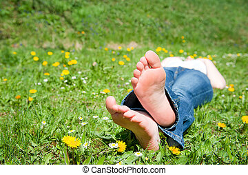 Feet of a young woman lying in a meadow