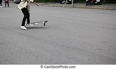 Feet of boys riding on a skateboard ride on asphalt. UltraHD stock footage.