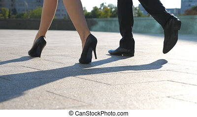 Feet of business man and woman in high heels shoes walking in urban street. Businessman and businesswoman commute to work together. Legs stepping to job. Colleagues going outdoor. Slow motion Close up