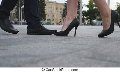 Feet of businessman in black shoes and businesswoman on high heels standing at city. Business couple meeting in urban street. Low angle view Close up Slow motion