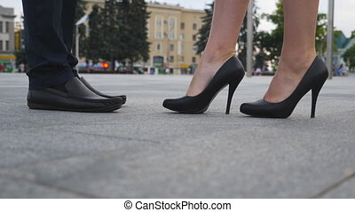 Feet of businessman in black shoes and businesswoman on high heels standing at city street. Business meeting between business partners outdoor. Low angle view Close up Slow motion